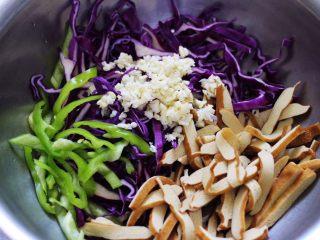 凉拌紫甘蓝香干,把切丝的紫甘蓝和青椒丝,焯过水的香干和搅碎的蒜末,放到一个容器里。