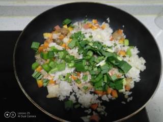 菠萝炒饭,加入蒜苗叶碎。