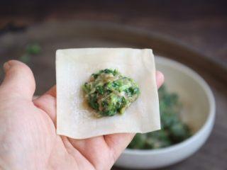 荠菜鸡肉馄饨,取一张云吞皮,放上适量的鸡肉荠菜馅儿。