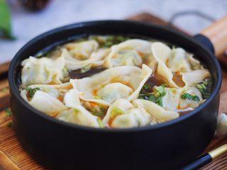 荠菜鸡肉馄饨,往汤碗里倒入煮小云吞的汤,用汤勺搅动一下碗里的汤,香菜、冬菜、小虾皮被滚汤烫熟,最后盛入小云吞即可。