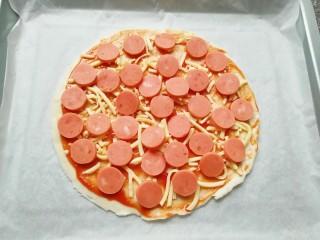 手抓饼披萨,铺上一层火腿肠。