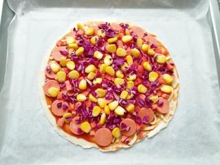 手抓饼披萨,均匀的撒上玉米粒、红萝卜和紫甘蓝。