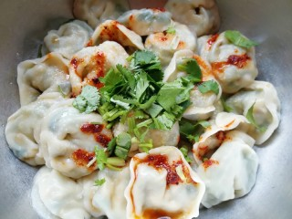 干拌饺子,煮好的饺子捞出,盛在大一点的容器里面,根据自己的口味放盐、鸡精、生抽、香醋、香油和辣椒油,最后放上切碎的香菜(不喜欢吃香菜可以不放,或者换成香葱也好吃)。