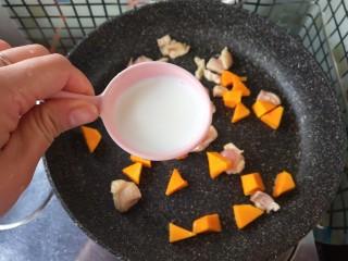 奶香南瓜鸡肉焗饭,放入牛奶,一起炒至牛奶吸变稠。