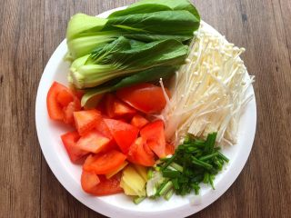 豆腐杂烩汤,把西红柿洗干净切成小块;再把上海青叶子剥下来清洗干净;金针菇切掉根部,清洗干净;生姜去皮洗干净切成姜片;葱清洗干净切葱段。