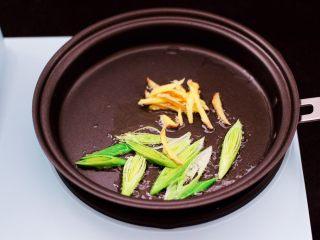 水萝卜粉丝炖桃花蛸,东菱早餐机的平底锅倒入花生油烧热后,先爆香姜和蒜苗。