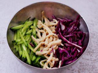 凉拌三丝,取一个大一点的容器,把切丝的紫甘蓝和黄瓜,焯过水的杏鲍菇放入。