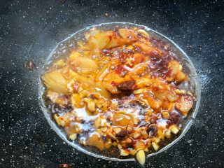 香辣牛蛙,热锅放入适量油,烧至6成热,放入郫县豆瓣酱小火炒出红油,再加入泡姜和蒜末炒出香味。