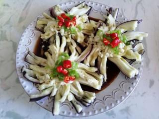 菊花茄子,将蒜末,青尖椒,小米椒依次放在茄子中间位置作为花蕊装饰