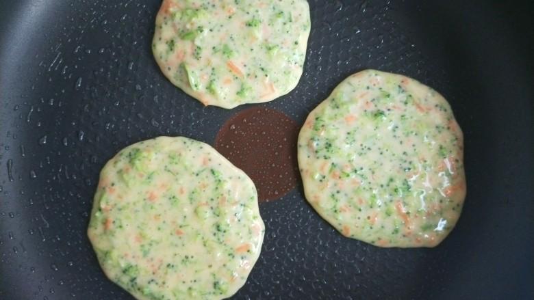 西兰花虾饼,平底锅刷油,小火,用勺子舀一勺面糊摊成圆饼。