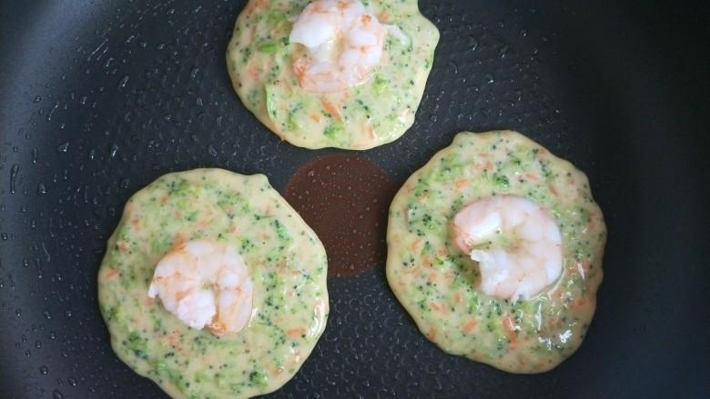 西兰花虾饼,然后把煮熟的虾仁放在饼的正中心。用力稍往下压一下。