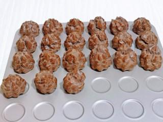 巧克力奶油泡芙,戴上隔热手套取出烤盘,放旁边晾凉。