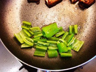 青椒煎排骨,倾斜锅体,用油慢炒青椒,加入少量盐。同时排骨的油也在慢慢渗析出来。