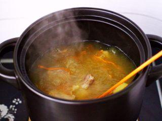 虫草花山药炖排骨,大火煮沸后,用勺子撇去浮末。