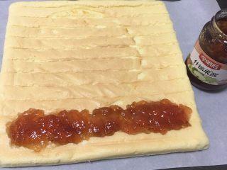 什锦果酱蛋糕卷,再用一张烤盘纸,蛋糕铺在纸上,表面放入什锦果酱。