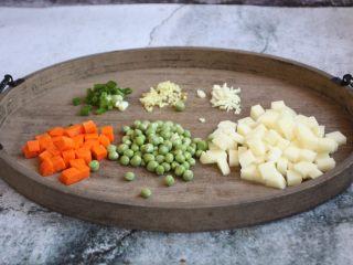 咖喱土豆鸡丁饭,将土豆切成丁、胡萝卜切成丁、豌豆清洗干净,葱切成葱花、姜切成姜末、蒜切成蒜末。
