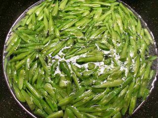 四季豆炒蛤蜊肉,热锅放入适量油,烧至8成热,把蒜末放入炒出香味。