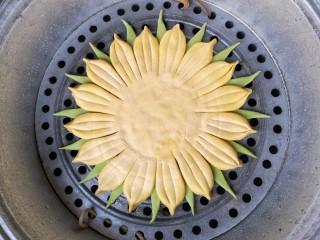 春暖花开,把菠菜面团做成的三角用水贴在葵花盘子造型花瓣空隙处做叶片,并放在抹了薄油的篦子上,上锅隔水大火蒸20分钟,关火后闷3分钟,出锅。