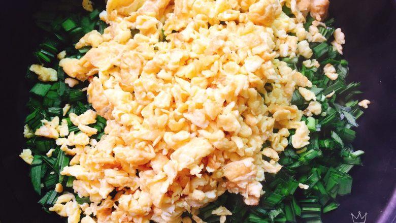 韭菜盒子+春天的味道,碗里放入切碎的韭菜末、倒入刚才炒制的鸡蛋碎,