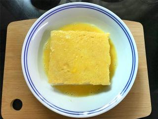 芒果酸奶吐司,把夹入水果的吐司放入鸡蛋液中,上下和四周都均匀地裹上一层蛋液。