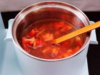 虾滑番茄豆干汤,早餐机的汤锅里加入适量的清水,把翻炒好的番茄倒入锅中。