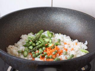 芦笋虾仁焗饭配冬阴功风味蒸烤鸡胸,放入芦笋、胡萝卜、豌豆,继续小火翻炒,,翻炒至蔬菜七成熟。