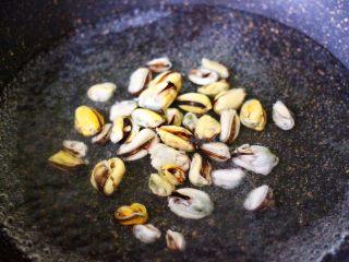 蒜香西葫芦海虹炒木耳,锅中倒入适量的清水煮沸后,加入一勺盐,把解冻的海虹肉进行焯水,焯过水的海虹沥干水分备用。