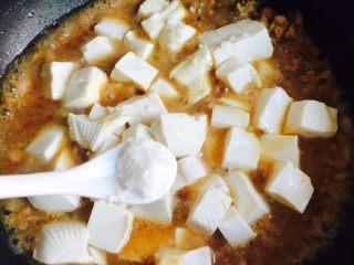 洋葱肉末烩豆腐,轻轻晃动锅子,加1小茶匙盐