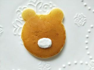 小熊酸奶软饼,另外用一个裱花袋,装一些刚才剩的酸奶,挤一个椭圆形。