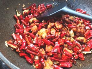 辣子鸡,倒入炸好的鸡块,翻炒出香味,使鸡块和辣椒的味道融合在一起,出锅装盘。
