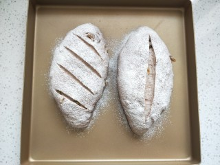全麦葡萄干核桃面包,当面团发至2倍大时,在面团表面喷水雾,筛上高筋粉,用锋利的小刀划出花纹。
