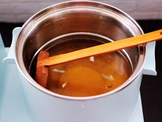 茼蒿羊肉卤味面,汤锅里加入适量的清水,把烧好的葱姜肉汤倒入锅中。