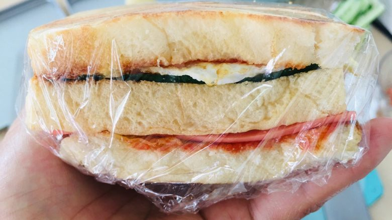 自制三明治,用保鲜膜包裹起来。