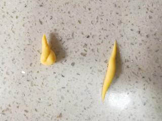 零色素卡通馒头可爱独角兽馒头,取大概1.5g黄色面团搓成如图右边两头尖的形状,然后对折扭麻花一样扭一起。如图左边形状。这样就做好一个独角兽的角了。一共做四个。面团重量只是参考,实际可以随手操作。