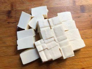 番茄烧豆腐,首先把豆腐冲洗一下改刀成小块。