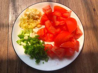 番茄烧豆腐,番茄清洗干净,切成小块,生姜去皮清洗干净切成末,蒜头去皮清洗干净切成末,葱清洗干净切成葱段,全部切好放入盘里待用。