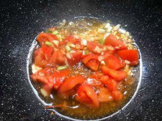 番茄烧豆腐,待番茄炒出汁以后,加入姜末、蒜末、葱白炒出香味。