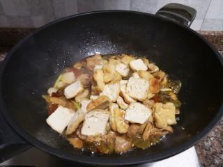 酸菜油豆腐烧肥肠,放入油豆腐翻炒片刻。