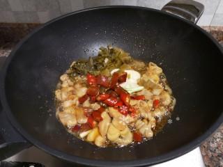 酸菜油豆腐烧肥肠,放入酸菜、大蒜、泡椒和泡姜翻炒片刻。