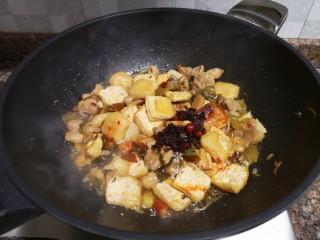 酸菜油豆腐烧肥肠,放入一勺老干妈油辣椒翻炒片刻。