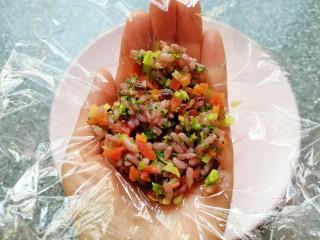 杂粮蔬菜饭团,手掌心里放上一张保鲜膜,舀入拌好的杂粮蔬菜饭,提起保鲜膜的四个角,用手捏好饭团。