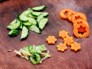 花蛤时蔬面,把黄瓜切成薄片,胡萝卜用模具刻成小花,也可以直接切成薄片,葱姜切丝备用。