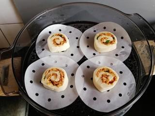 肉松馒头卷,横过来放在馒头纸上,蒸锅内加入适量的温水,放入馒头胚进行发酵