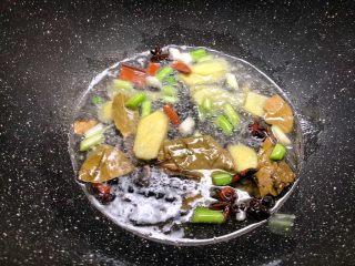 萝卜烧牛腩,锅里放入适量油,先把葱白和姜片放入炒出香味,再把八角、桂皮、香叶放入炒香。