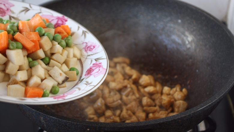 鸡丁炒豌豆杏鲍菇,翻炒均匀鸡丁后放入杏鲍菇和胡萝卜、豌豆。