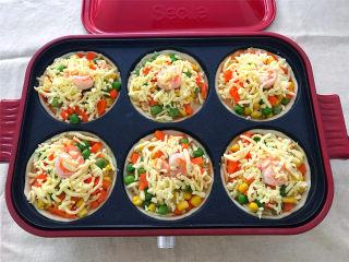 鲜虾小披萨,把烤盘放入预热好的多功能锅中,大火烤5分钟后转中小火,烤至马苏里拉芝士融化后再烤5分钟即可。