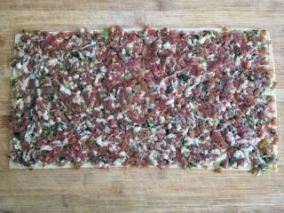 糖醋东北肉签子,豆腐皮铺在菜板上,将调好的肉馅均匀平铺在豆腐皮一面。