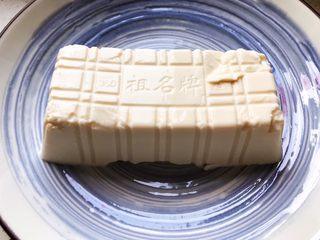 鲍鱼干贝XO酱拌香椿皮蛋豆腐,取出豆腐放入碗内,静置