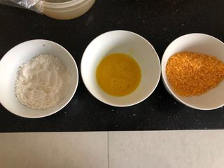 土豆凤尾虾球,用三个碗分别加入面粉,蛋液喝面包糠,每一个凤尾虾球按照面粉,蛋液和面包糠的顺序沾好。然后摆在放有油纸的烤盘上。