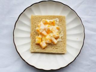 好吃到爆的酸奶芒果土司,取2勺芒果酸奶抹在土司上。